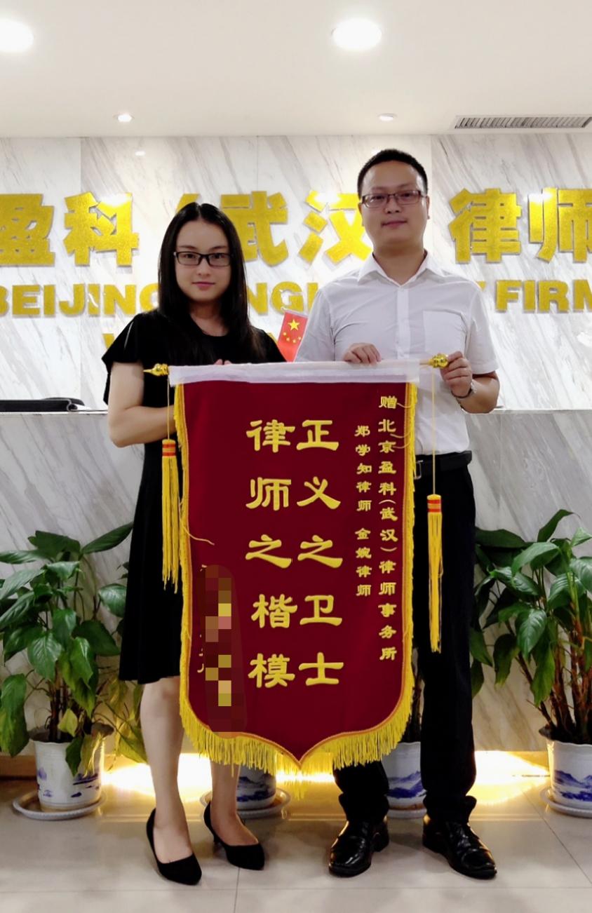 郑学知律师和其助手金婉律师接受当事人送来锦旗